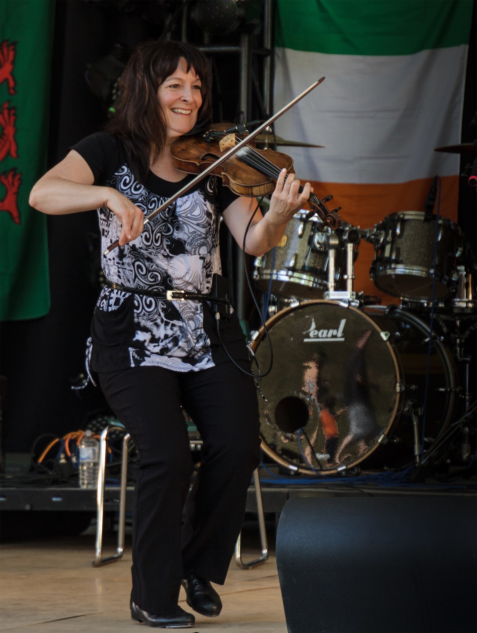 Cindy Thompson similing, step dancing and playing the fiddle on stage in front of a set of drums.